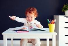 Den lyckliga rödhåriga mannen behandla som ett barn pojketeckningen i framkallande bok på skrivbordet Fotografering för Bildbyråer