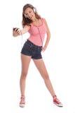 den lyckliga roliga flickan har lagt benen på ryggen tonårs- lång musik royaltyfria bilder