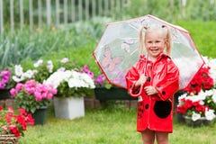 Den lyckliga roliga nätta lilla flickan i röd regnrock med paraplyet som in går, parkerar sommar Arkivbild