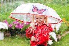 Den lyckliga roliga nätta lilla flickan i röd regnrock med paraplyet som in går, parkerar sommar Royaltyfri Fotografi