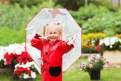 Den lyckliga roliga nätta lilla flickan i röd regnrock med paraplyet som in går, parkerar sommar Royaltyfria Bilder