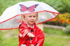 Den lyckliga roliga nätta lilla flickan i röd regnrock med paraplyet som in går, parkerar sommar Arkivfoton