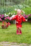 Den lyckliga roliga nätta lilla flickan i röd regnrock med paraplyet som in går, parkerar sommar Royaltyfri Foto