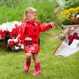 Den lyckliga roliga nätta lilla flickan i röd regnrock med paraplyet som in går, parkerar sommar Arkivfoto