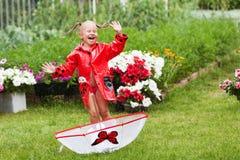Den lyckliga roliga nätta lilla flickan i röd regnrock med paraplyet som in går, parkerar sommar Fotografering för Bildbyråer