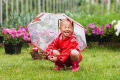 Den lyckliga roliga nätta lilla flickan i röd regnrock med paraplyet som in går, parkerar sommar Arkivbilder