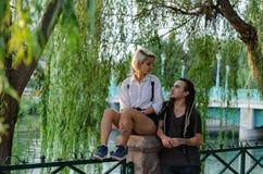 Den lyckliga romantiker kopplar ihop på parkera, dem ser de fotografering för bildbyråer