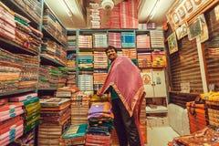 Den lyckliga säljaren med textilen väntar på kunder i traditionell marknad med kvinnliga kläder Royaltyfri Fotografi
