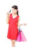 Den lyckliga shoppingkvinnan tar kreditkorten och påsen Arkivbilder