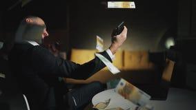 Den lyckliga skäggiga affärsmannen arbetar hemma med bärbara datorn och gör ett lyckat avtal eller segrar stora pengar Pengar fal arkivfilmer