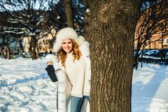 Den lyckliga skämtsamma kvinnan med kastar snöboll den utomhus- ståenden royaltyfria bilder