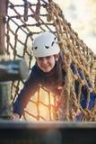 Den lyckliga skolaflickan som tycker om aktivitet i ett klättringaffärsföretag, parkerar Arkivfoton