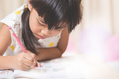 Den lyckliga skolflickan arbetar på hennes läxa, skriver något i hennes n Royaltyfri Foto