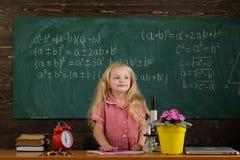 Den lyckliga skolflickan har kurs i grundskola för barn mellan 5 och 11 år Skolflickaleende på den svart tavlan för klassrum royaltyfria bilder