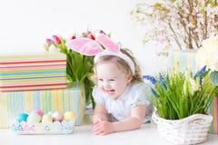 Den lyckliga skratta litet barnflickan med ägg fjädrar blommor Royaltyfri Bild