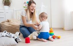 Den lyckliga skratta modern som spelar med hennes 10 gamla månader, behandla som ett barn sonen Royaltyfri Bild