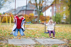 Den lyckliga skratta pojken och behandla som ett barn systern som spelar på gunga Royaltyfri Fotografi