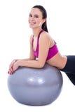 Den lyckliga slanka kvinnan i sportar bär med konditionbollen som isoleras på wh Royaltyfri Bild