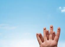 Den lyckliga smileyen fingrar se klar copyspace för blå himmel Arkivbild