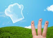 Den lyckliga smileyframsidan fingrar se illustrationen av kockhatten Royaltyfri Fotografi