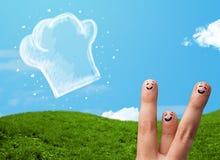 Den lyckliga smileyframsidan fingrar se illustrationen av kockhatten Arkivfoto