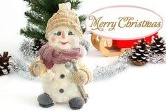 Den lyckliga snögubben som förbi omges, sörjer kottar Snögubbe med jultomten släde arkivbilder