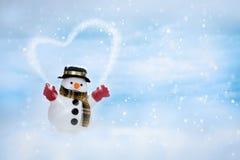 Den lyckliga snögubben står i vinterjullandskap arkivfoton