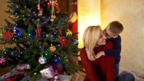 Den lyckliga sonen kramar mamman under träd för nytt år stock video