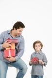 Den lyckliga sonen som kramar hans fader och, ger honom gåvan Faderdag, familjferie Arkivfoton