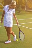Den lyckliga sportflickan står med racket på domstolen på den soliga sommardagen Royaltyfri Bild