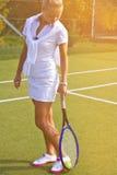 Den lyckliga sportflickan står med racket på domstolen på den soliga sommardagen Arkivfoton