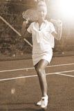 Den lyckliga sportflickan står med racket på domstolen på den soliga sommardagen Arkivbilder