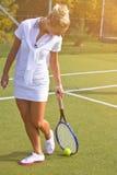 Den lyckliga sportflickan står med racket på domstolen på den soliga sommardagen Royaltyfri Foto