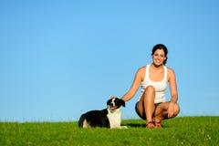 Den lyckliga sportiga kvinnan som tar öva, vilar med hennes hund Royaltyfri Foto