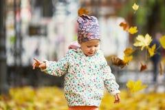 Den lyckliga stads- lilla flickan som går i stadshöst, parkerar Royaltyfria Bilder