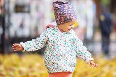 Den lyckliga stads- lilla flickan som går i stadshöst, parkerar Arkivfoton