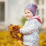 Den lyckliga stads- lilla flickan som går i stadshöst, parkerar Royaltyfri Foto