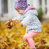 Den lyckliga stads- lilla flickan som går i stadshöst, parkerar Arkivbild