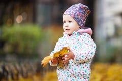 Den lyckliga stads- lilla flickan som går i stadshöst, parkerar Royaltyfria Foton