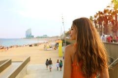 Den lyckliga stadskvinnan går till stranden på solnedgången Innehåll lutning- och urklippmaskeringen Arkivfoton