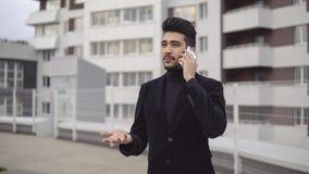 Den lyckliga stilfulla affärsmannen hör goda nyheter på telefonen och jublar med lyckliga sinnesrörelser utomhus nära kontorsbygg Royaltyfri Foto
