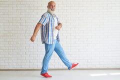 Den lyckliga stilfulla pensionären går i ljust vitt rum arkivbild