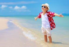 Den lyckliga stilfulla pojken tycker om liv på sommarstranden Royaltyfri Bild