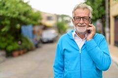 Den lyckliga stiliga pensionären uppsökte mannen som ler, medan tala på mobil arkivfoto