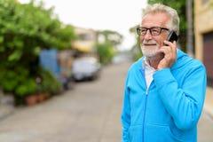 Den lyckliga stiliga pensionären uppsökte mannen som ler, medan tala på mobil royaltyfri fotografi