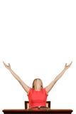 Den lyckliga studenten med armar lyftte sammanträde på tabellen fotografering för bildbyråer
