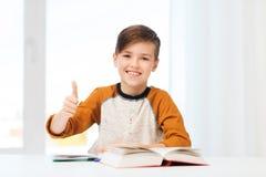 Den lyckliga studentpojken med lärobokvisning tummar upp Arkivbilder