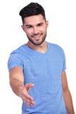 Den lyckliga tillfälliga mannen välkomnar dig med en handskakning Fotografering för Bildbyråer