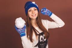 Den lyckliga tonåriga flickan med kastar snöboll fotografering för bildbyråer