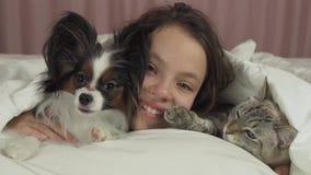 Den lyckliga tonåriga flickan meddelar med hunden Papillon och den thailändska katten i video för sängmateriellängd i fot räknat stock video